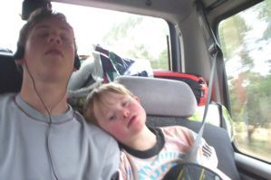 Jacob, a kid with Down Syndrome, age 5, enjoying the rest on his big brother's shoulder while on a long country drive.