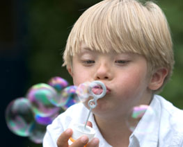 Down syndrome child blowing bubbles