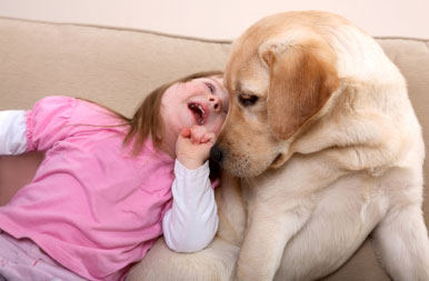Down syndrome girl playing with dog