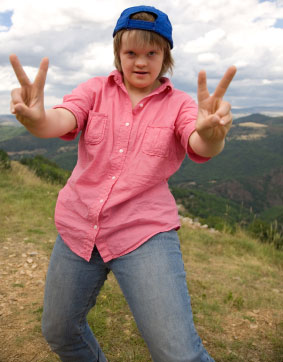 Adolescent girl with Down syndrome on top of mountain