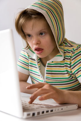 Girl child with Downs syndrome on laptop
