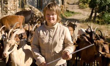Teenage girl with Downs syndrome on a farm with a goat herd